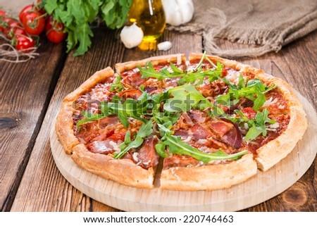 Homemade Ham Pizza slices (with rocket, fresh tomatoes, garlic and cheese) - stock photo