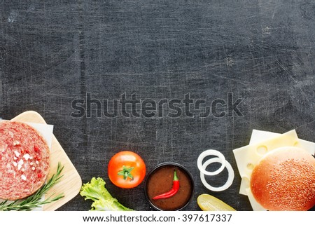 Homemade hamburger ingredients. Raw minced beef (patty), fresh bun, slice of cheese, tomato, onion rings, pickle, lettuce, herbs and BBQ sauce. Black board background. Space for text. - stock photo