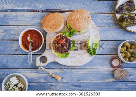 Homemade hamburger with chicken and cheese, tomatoes sauce plate from above on rustic cutting board over on blue wooden chalkboard. Rustic style. - stock photo