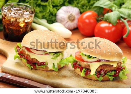 Homemade hamburger with fresh vegetables and cheese on wooden cutting board - stock photo