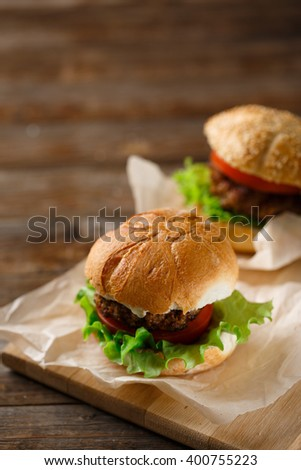 Homemade hamburgers and french fries on wooden table - stock photo