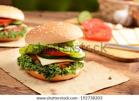 Homemade hamburgers with cheese, tomatoes and cucumbers - stock photo
