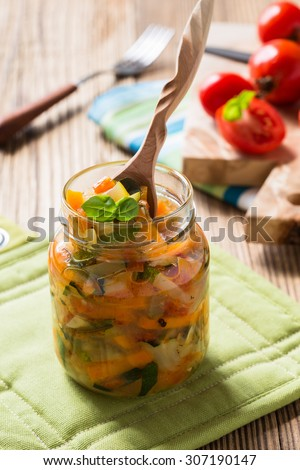 Homemade healthy vegetable  preserves in glass jar, zucchini, carrots, onions and tomatoes salad - stock photo