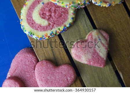Homemade heart shaped and colorful cookies with small tea cup on blue background - stock photo
