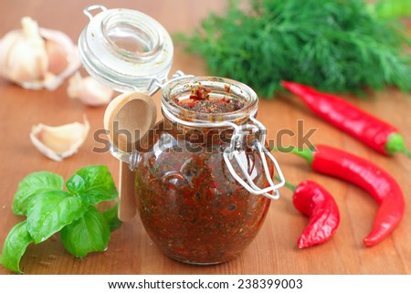 Homemade hot spicy adjika dip in glass jar on wooden background - stock photo