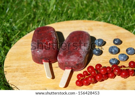 Homemade ice cream pops with different berries: red currant, blueberry, strawberry and blackberry - stock photo