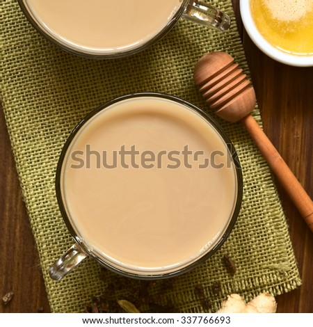 Homemade Indian Masala Chai Tea made of black tea, a variety of spices and mixed with milk, honey, photographed overhead with natural light (Selective Focus, Focus on the top of the tea) - stock photo