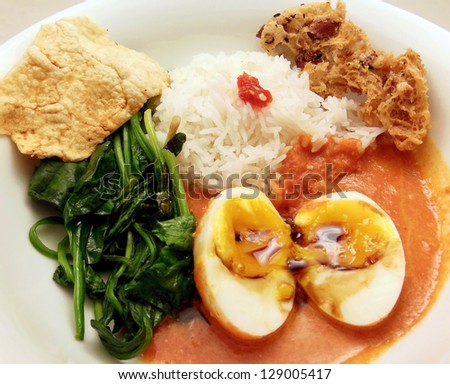 Homemade Indonesian dinner with eggs in spicy coconut and tomato sauce, spinach, rice, hot sauce, emping and rempeyek (peanut cracker). - stock photo