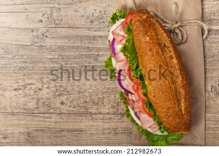 Homemade Italian Sub Sandwich with Salami, Tomato, and Lettuce. Selective focus.  - stock photo