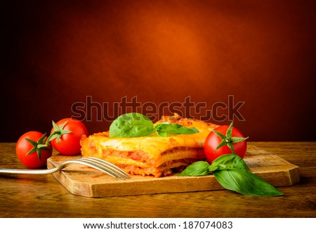 homemade lasagne bolognese with fresh basil and tomatoes - stock photo
