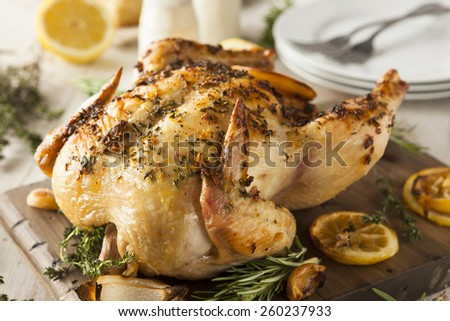 Homemade Lemon and Herb Whole Chicken on a Cutting Board - stock photo