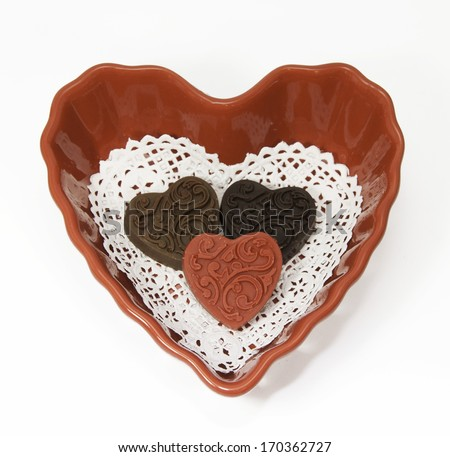 Homemade light, dark, and red chocolate hearts on a white lace doily in a red heart shaped bowl against a white background - stock photo