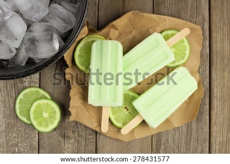 Homemade lime yogurt popsicles with fresh lime slices on paper with rustic wood background - stock photo