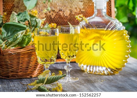 Homemade liqueur made �¢??�¢??of honey and lime in summer garden - stock photo