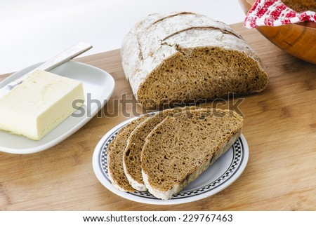 Homemade loaf of Rye Bread sliced with butter - stock photo