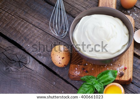Homemade mayonnaise sauce in a bowl on a wooden background, with space for text - stock photo