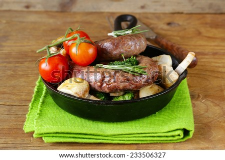 homemade meat sausages with vegetables garnish (broccoli and mushrooms) - stock photo