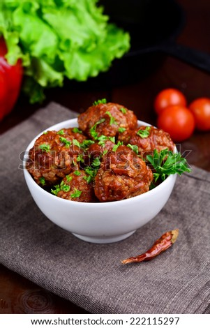 Homemade meatballs with tomato sauce garnished with chopped parsley in white bowl on brown napkin. Fresh vegetables on background - stock photo