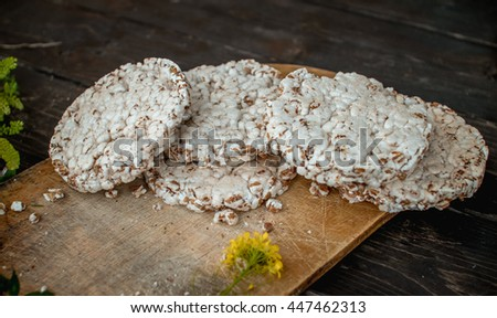 Homemade milk and tasty crispbread on wooden table background. spilled milk and wildflowers - stock photo