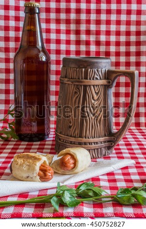Homemade Mini hot dogs (sausage in pastry) on napkin with a bottle of dark beer and earthenware mug on a plaid background - stock photo
