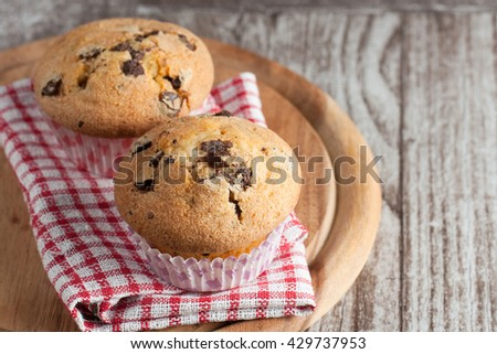Homemade muffins with chocolate chips and blueberries with a glass of milk and coffee. Cupcake with chocolate. - stock photo