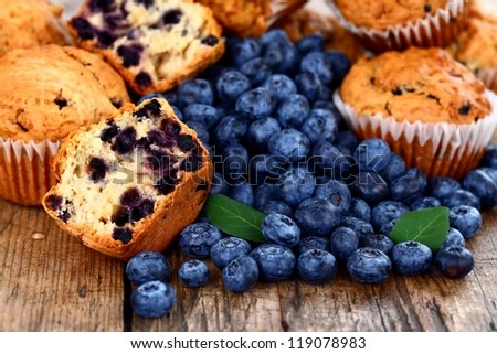 Homemade muffins with fresh blueberries on wooden table - stock photo