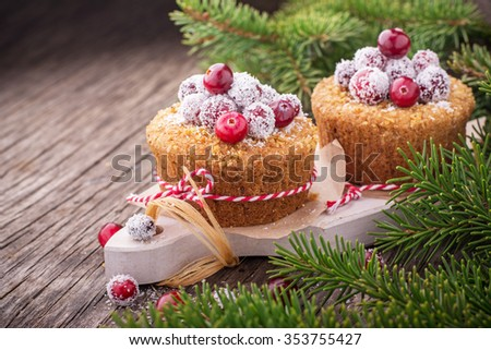 Homemade muffins with golden ripe cranberries and coconut on a simple wooden background with fir branches as decoration. selective Focus - stock photo