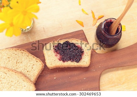 homemade mulberry jam on homemade bread with yellow flowers. - stock photo