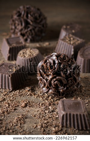Homemade natural chocolate candies with chips on wooden background. - stock photo