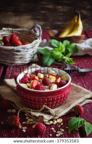 Homemade oatmeal cereal with fresh raspberries, strawberries and banana in a ceramic bowl. Morning breakfast. Rustic style .Bio healthy food. Selective focus - stock photo