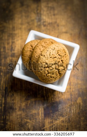 Homemade oatmeal cookies in white bowl on rustic wooden background - stock photo