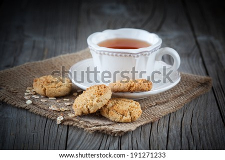 Homemade oatmeal cookies  with a cup of tea on old wooden background - stock photo