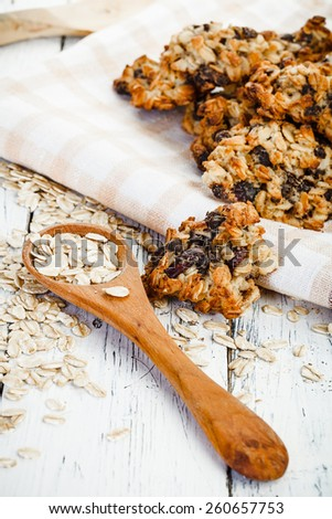 homemade oatmeal cookies, wooden spoon with oat and old textile tablecloth on old white wooden table - stock photo