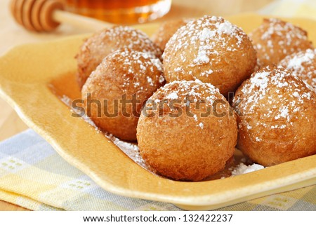 Homemade pancake balls (cinnamon recipe) deep fried - by dropping spoonfuls of batter into fryer - and sprinkled with powdered sugar.  Macro with shallow dof. - stock photo