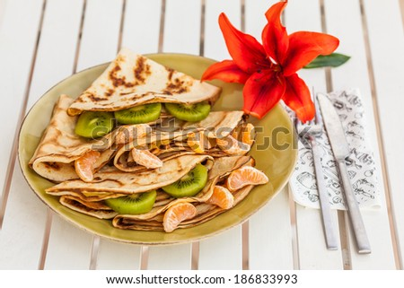 Homemade pancakes filled with jam and fruits - stock photo