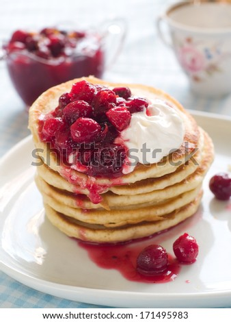 Homemade pancakes with cranberry sauce and sour cream, selective focus - stock photo