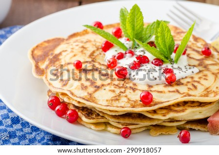 Homemade pancakes with cream, currant and baked rhubarb, delicious and simple seasonal recipe - stock photo