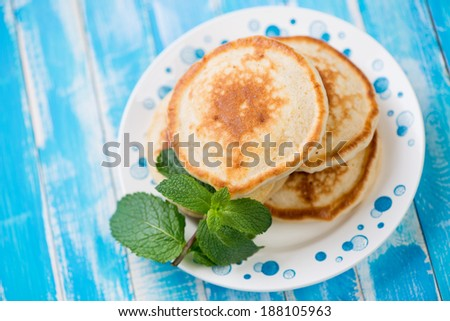 Homemade pancakes with mint leaves on a glass plate, above view - stock photo