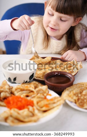 homemade pancakes with various fillings. Little girl with pancakes. snack for Shrovetide. - stock photo