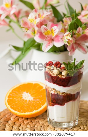 Homemade parfait served in high glasses with yogurt and organic raspberries, nuts and mint. Delicious snack for healthy life.  Breakfast on a straw tablemat with spoons and flowers and half of orange - stock photo