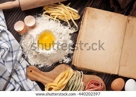 Homemade pasta cooking and vintage cooking book on wooden table. Top view with copy space - stock photo