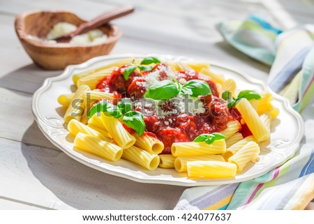 Homemade pasta penne with tomato sauce, basil and parmesan - stock photo