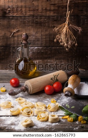 Homemade pasta ravioli on old wooden table with flour, basil, tomatoes, olive oil and vintage kitchen accessories. See series - stock photo