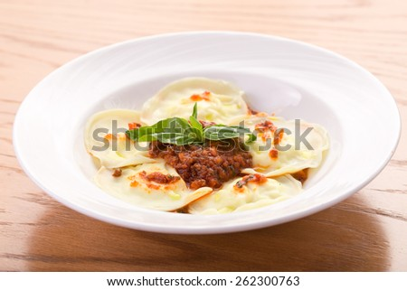 Homemade pasta ravioli with meat, tomato and basil on white plate - stock photo
