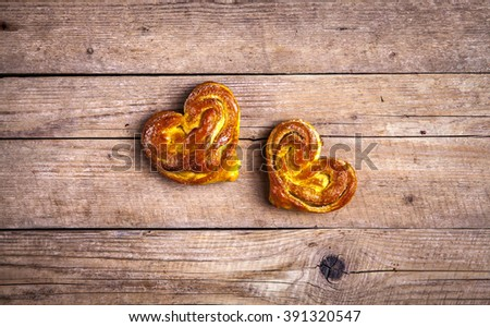 Homemade pastries. Bun heart on wooden background. Food - stock photo
