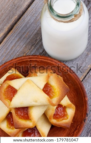 Homemade Pastry Jam Wrapped and Bottle of Milk closeup on Rustic Wooden background. Top View - stock photo