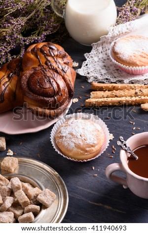 Homemade pastry with cocoa and milk on wooden table, decorated with heather. - stock photo
