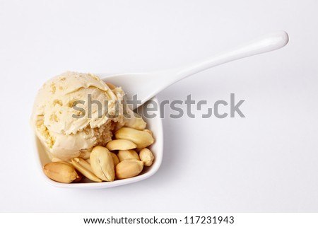 Homemade peanut butter ice cream with peanuts and a spoon - stock photo