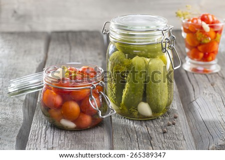 Homemade pickles Cucumbers, Tomatos, Custard squash in brine with garlic, dill and horseradish on woodboard - stock photo