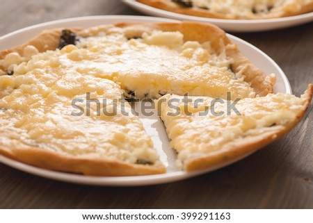 Homemade pie with cut slice in a white plate on wooden table, closeup, selective focus - stock photo